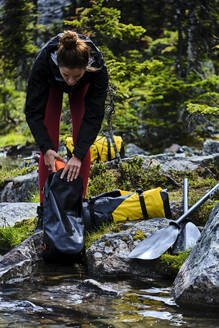 A woman unpacks her gear to prepare to packrat across Cirque Lake. - CAVF72770