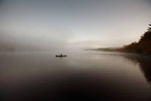 Solo paddling on a misty pond at sunrise. - CAVF72854