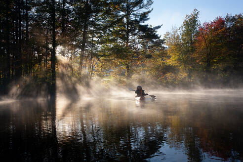 Solo paddling on a misty pond at sunrise. - CAVF72866