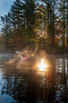Solo paddling on a misty pond at sunrise. - CAVF72872