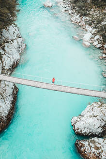 Aerial shot of young woman standing on bridge above whitewater river - CAVF72896