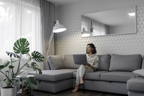 Woman with laptop sitting on the couch at home looking out of window - KMKF01181