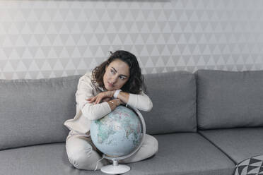 Portrait of woman sitting on the couch at home leaning on globe while looking at distance - KMKF01184