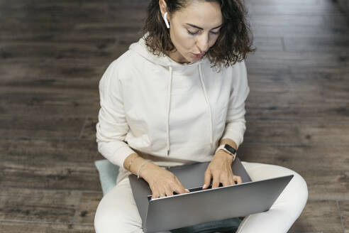 Woman sitting on the floor at home using laptop and earphones - KMKF01187