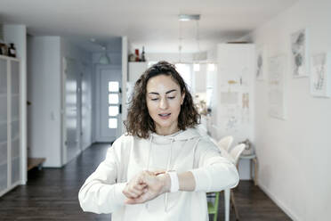 Portrait of woman looking at her smartwatch at home - KMKF01190