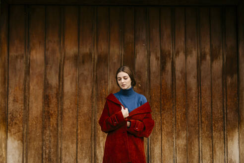 Close up portrait of woman with blue turtleneck pullover and red coat in front of a wooden door - TCEF00006