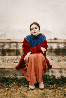 Close up portrait of woman with blue turtleneck pullover and red coat sitting on a step - TCEF00009