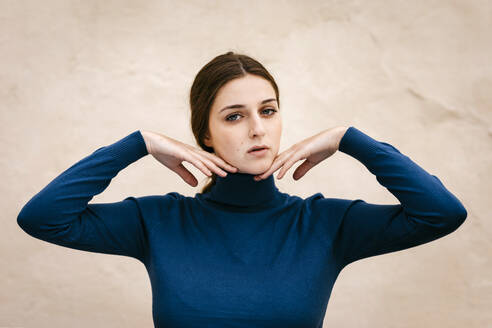 Close up portrait of woman with blue turtleneck pullover, hands on chin - TCEF00015