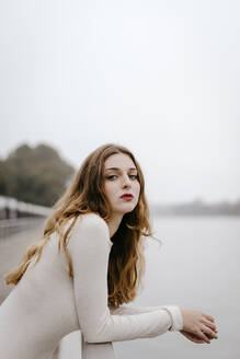 Portrait of young woman wearing white dress, leaning on railing on rainy day - TCEF00021