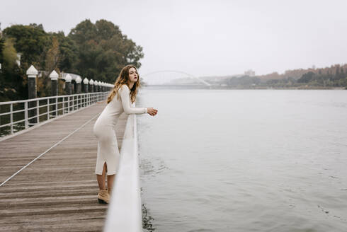 Portrait of young woman wearing white dress, leaning on railing on rainy day - TCEF00024