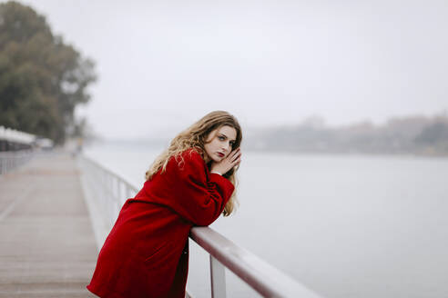Portrait of young woman wearing red coat, leaning on railing on rainy day - TCEF00027
