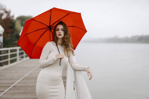 Portrait of young woman with red umbrella, leaning on railing during rainy day - TCEF00033