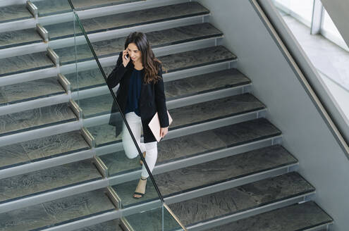 Businesswoman on stairs talking on the phone - DGOF00028