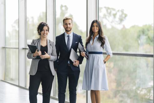 Portrait of confident business team holding portable devices - DGOF00034