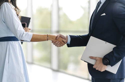 Close-up of businessman and businesswoman shaking hands - DGOF00037