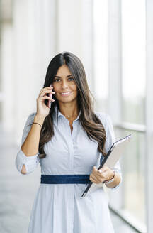 Portrait of smiling businesswoman talking on the phone - DGOF00049