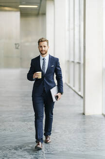 Portrait of businessman with takeaway coffee on the go - DGOF00052