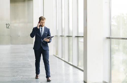 Businessman holding tablet talking on the phone - DGOF00055