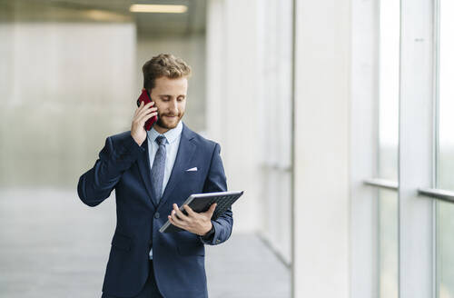 Businessman holding tablet talking on the phone - DGOF00058