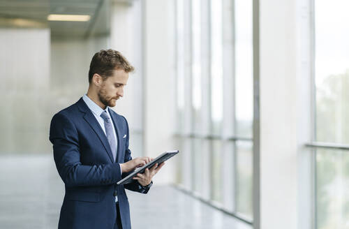 Businesman using tablet at the window - DGOF00061
