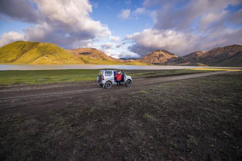 Woman traveller enjoying scenic view beside vehicle, Landmannalaugar, Highlands, Iceland - CUF54545