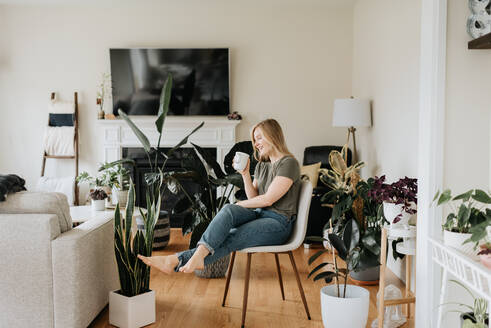 Woman relaxing with warm beverage in room full of house plants - ISF23649