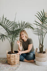 Woman admiring her house plant - ISF23667