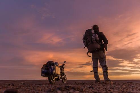 Motorcyclist enjoying sunset in desert, Arequipa, Peru - ISF23706