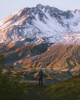 Hiker admiring Mount St Helens National Monument from afar, Washington, USA - ISF23715