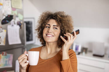 Woman holding cell phone and coffee cup at home - FMKF06073