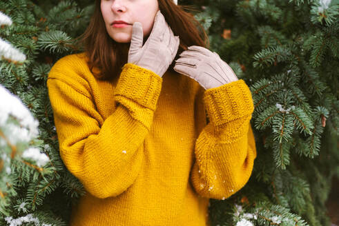 Woman looking away while standing by snow covered trees - CAVF73237