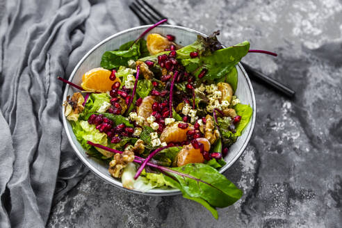 Winter salad with lettuce, tangerines, walnuts, feta and pomegranate seeds - SARF04425