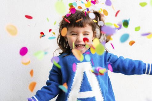 Happy little girl blowing the confetti at a party in front of a white wall - GEMF03411