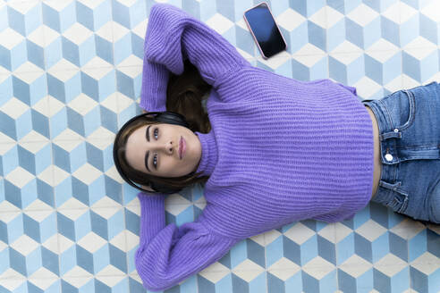 Portrait of happy young woman lying on the floor listening music with headphones - ERRF02601