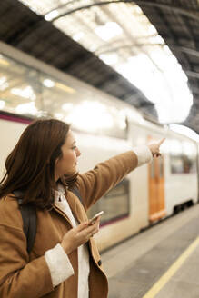 Young woman with cell phone at the train station pointing her finger - VABF02494