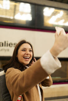 Happy young woman taking a selfie at the train station - VABF02497