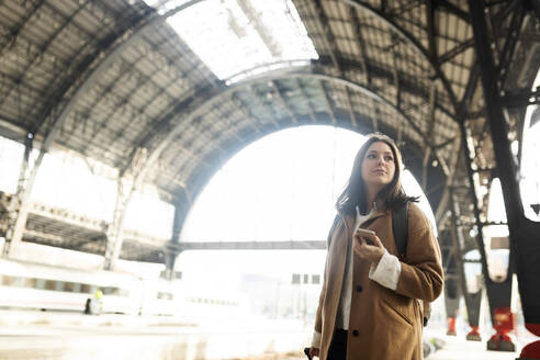 Young woman with cell phone at the train station looking around - VABF02503