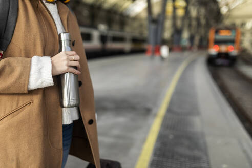 Close-up of woman holding thermos flask at the train station - VABF02506