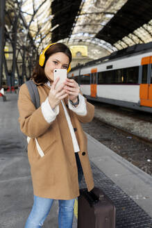 Young woman with headphones and cell phone at the train station - VABF02509
