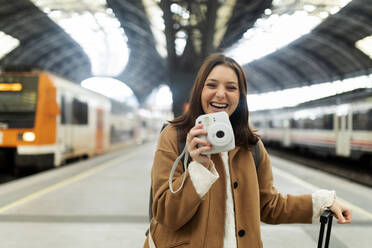 Happy young woman with camera at the train station - VABF02512