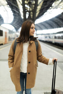 Young woman with suitcase at the train station looking around - VABF02515