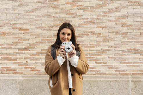 Portrait of smiling young woman with camera in front of a brick wall - VABF02521