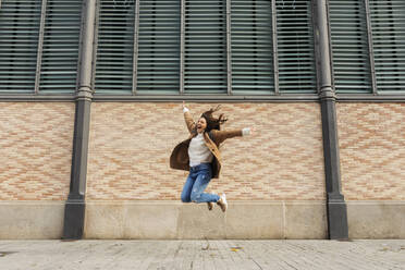 Excited young woman jumping in the city - VABF02527
