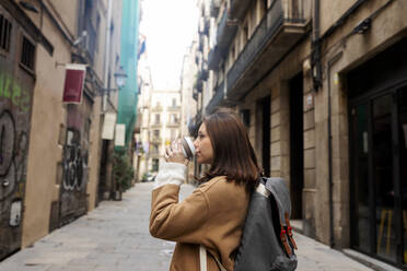 Young woman with takeaway coffee in the city, Barcelona, Spain - VABF02539