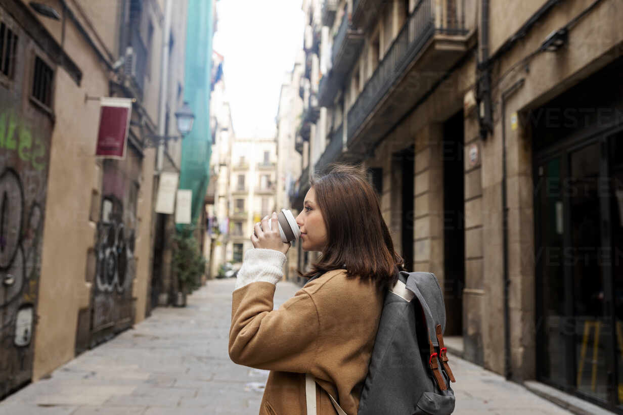 Young woman with takeaway coffee in the city, Barcelona, Spain - VABF02539 - Valentina Barreto/Westend61