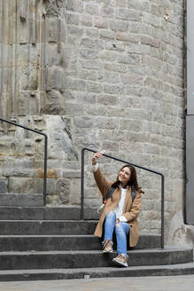 Smiling young woman sitting on stairs in the city taking a selfie, Barcelona, Spain - VABF02542