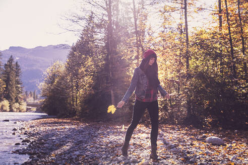 Woman wearing red woolly hat and denim jacket walking at riverside in autumn - DHEF00015