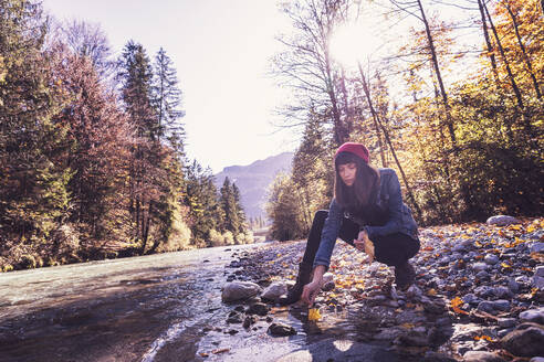 Woman wearing red woolly hat and denim jacket at riverside - DHEF00018