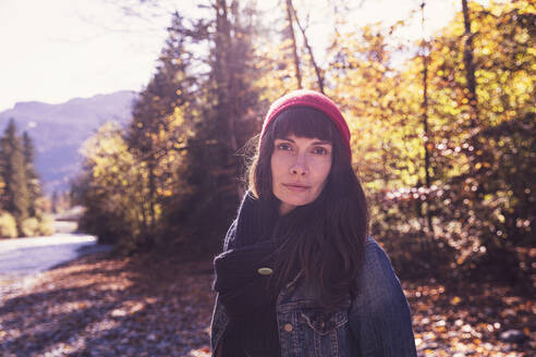 Woman wearing red woolly hat and denim jacket at riverside in autumn - DHEF00027