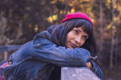Woman wearing red woolly hat and denim jacket looking sideways - DHEF00033
